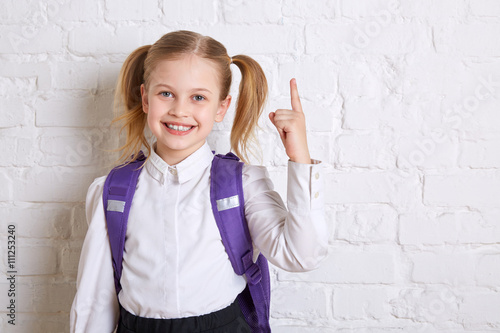 Fotografía  Cute smiling schoolgirl in uniform standing on light  background and showing  thumb up