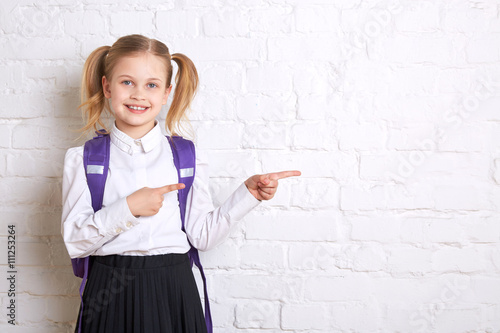 Fotografía  Cute smiling schoolgirl in uniform standing on light  background and showing  thumbs to the side