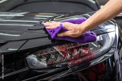 Car detailing series : Closeup of hand cleaning black car