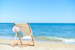 Deckchair and female hat on stunning tropical beach vacation background