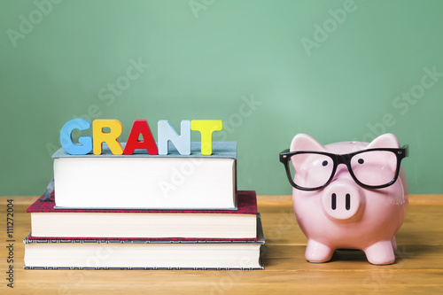 Fotografering  Education grant theme with pink piggy bank on top of books with chalkboard in th