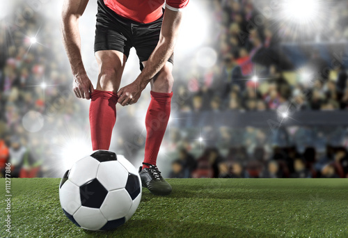 football player with ball wearing black shoes adjusting his red sock standing on stadium pitch