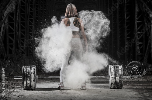 Rear view of woman working out with weights in the gym
