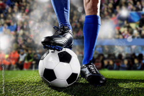 legs and feet of football player in blue socks and black shoes standing with the ball playing match at soccer stadium