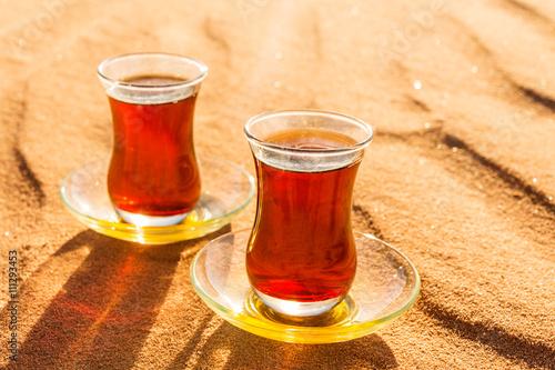 Photo  tea in traditional glasses  on desert at sunset