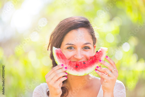 Beautiful young woman at park eating a slice of watermelon Poster