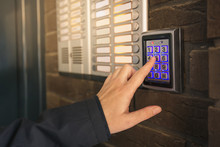 Woman Dialing Passcode On Intercom Security Keypad