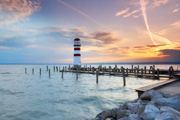 FototapetaLeuchtturm am Ende eines Holzsteges, See zum Sonnenuntergang