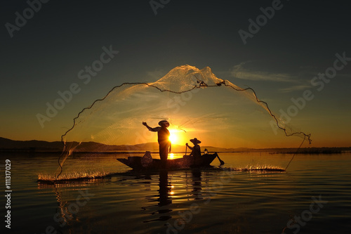 Canvas Print Fisherman of asian people at Lake in action when fishing during sunrise