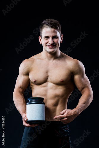Fotografia  Bodybuilder holding a black plastic jar blank white label whey protein and point