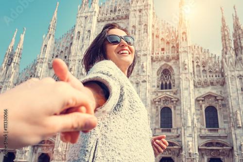 Fotografie, Obraz  Smiling woman hold his boyfriend hand on Duomo di Milano backgro