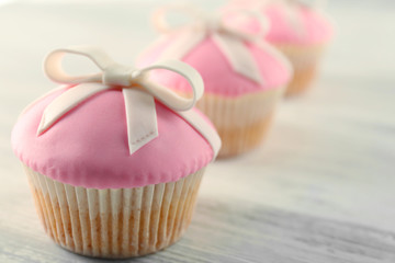 Tasty cupcakes with bow,  on light background