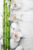 Beautiful spa composition with bamboo on light wooden background