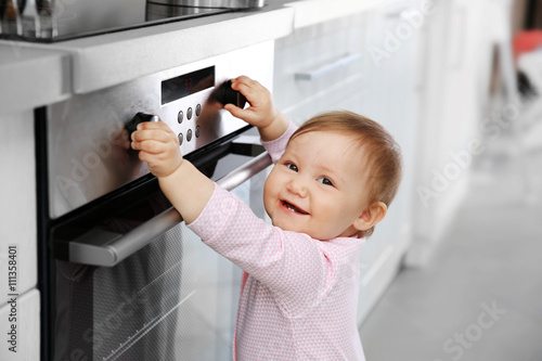 Fotografía  Little child playing with electric stove in the kitchen