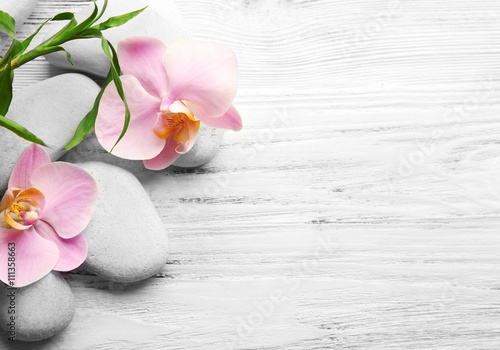 Poster Spa Spa stones, bamboo stack and orchid flowers on wooden background