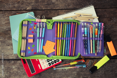 Fotografía Pencil case with various stationery on old  wooden table