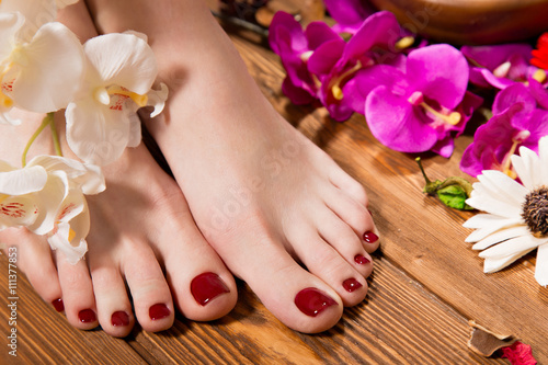 Beautiful classic red pedicure on female hand. Close-up. Poster