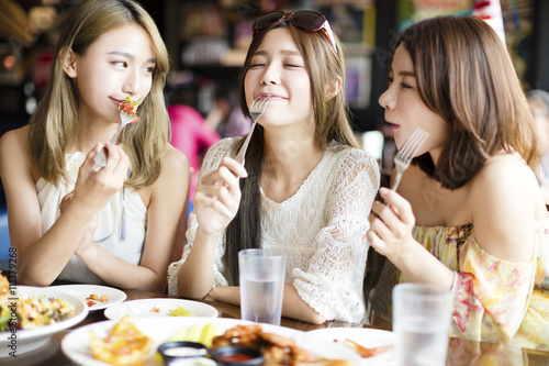 Spoed Foto op Canvas Kruidenierswinkel young woman Friends Enjoying Meal in the Restaurant