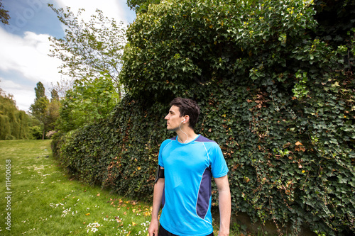 Running workout man with mp3 music player listening to music with