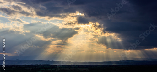 Fotografie, Obraz  Stormy clouds with radiating sunbeams above countryside.
