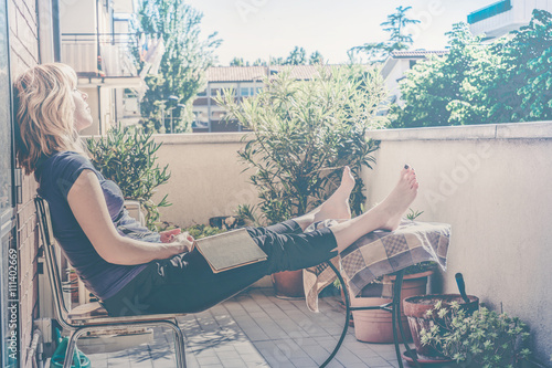 Foto lazy woman relaxing sitting on balcony falling asleep with a book in hand - vint