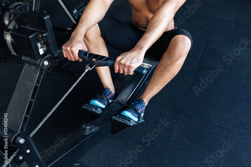 Fotografie, Obraz  Muscular fitness man using rowing machine in the gym
