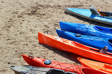 Colorful Kayaks And Canoes On Sandy Beach