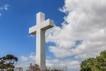 Mt. Helix Cross With Fence Railing, Foliage And A Cloudy Blue Sky In La Mesa, A City In San Diego, California.