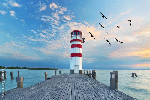 zum Sonnenuntergang am Leuchtturm am See Fototapet