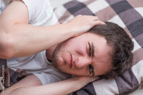 Fotografering  Junger Mann kann nicht schlafen, grimmiger Blick