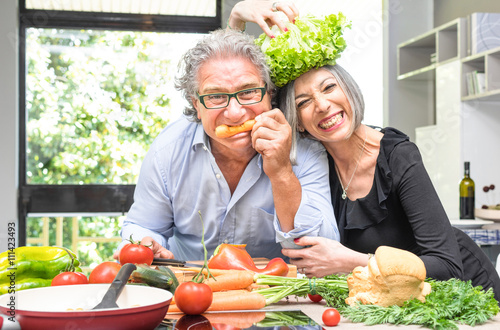 Photo  Senior couple having fun in kitchen with healthy food - Retired poeple cooking t