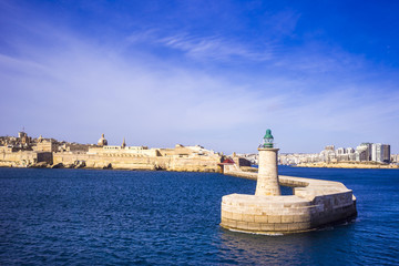 FototapetaValletta, Malta - old Lighthouse and Breakwater bridge in the morning with blue sky