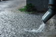 Rain water flowing from a metal downspout during a heavy rain. concept of protection against heavy rains