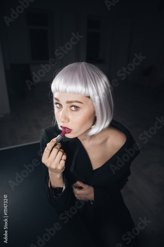 Photo  Attractive woman in blonde wig applying lipstick in dressing room