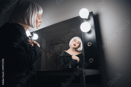 Plagát  Woman in blonde wig sitting near mirror in dressing room