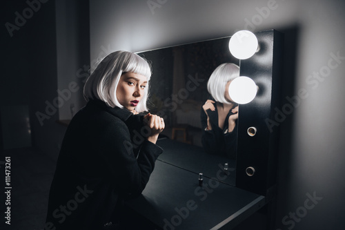 Woman in blonde wig and black coat in dressing room Canvas Print