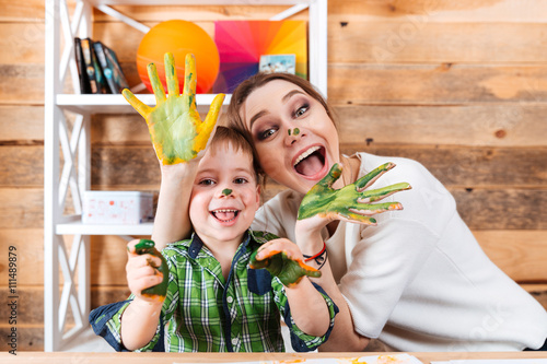 Cheerful mother and son with painted hands having fun together