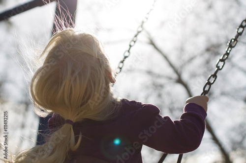 Rear view of a girl sitting on a swing