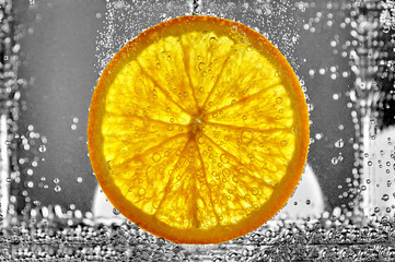 Fototapeta Owoce Juicy slice of orange fruit in water