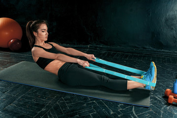 Fototapeta Fitness / Siłownia The brunette athletic woman exercising with rubber tape