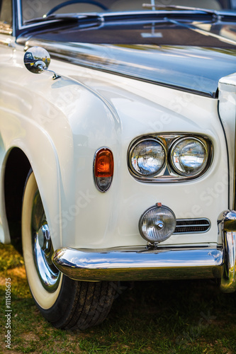 Close-up of the front part of the luxury retro car. Old vintage car. Selective focus on the car's headlight.