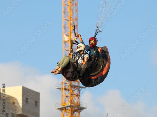 Poster Luchtsport A man and woman paragliding in the mediterranean sky