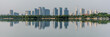 Panorama of the city and trees reflected in calm water. Wide panorama of skyscrapers on a background of clear sky. Panorama of a modern city