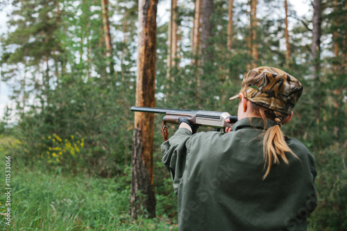 Foto op Aluminium Jacht Woman hunter with a gun. Hunting in the woods.