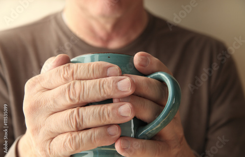 Valokuva  Older man warms his hands with a cup of hot coffee.