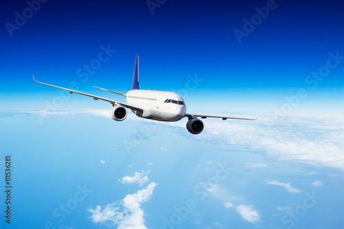 Commercial jet plane flying above clouds Canvas