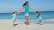 Happy family with little kids having fun at exotic beach on sunny day