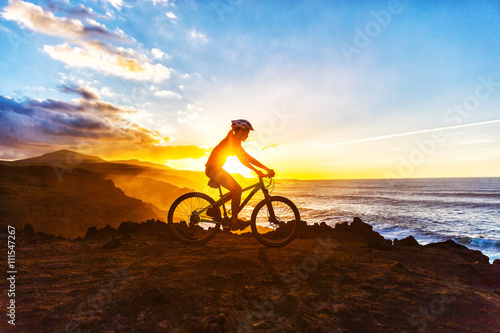 obraz dibond Mountain biking MTB cyclist woman cycling on bike trail on coast at sunset. Person on bike by sea in sportswear with bicycle enjoying healthy active lifestyle in beautiful nature.