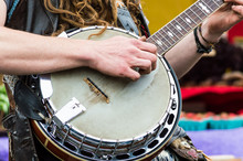 Close Up Of A Banjo Player Playing Music For An Audience At A Farmers Market.