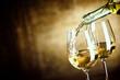 Leinwanddruck Bild - Pouring two glasses of white wine from a bottle